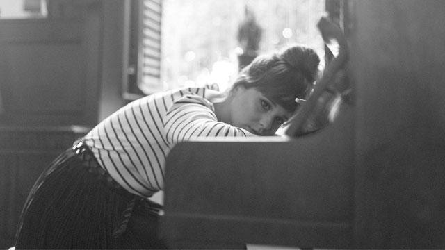 ピアノにもたれかかる女性